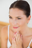 Smiling brunette meditating with hands together