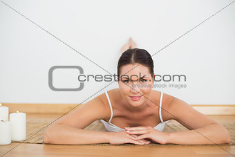 Smiling brunette lying on floor looking at camera