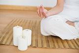 Woman sitting in lotus pose beside white candles
