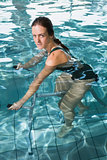 Fit brunette using underwater exercise bike