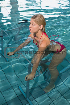 Fit blonde using underwater exercise bike