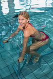 Fit blonde using underwater exercise bike smiling at camera