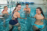 Fitness class doing aqua aerobics on exercise bikes