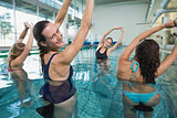 Female fitness class doing aqua aerobics on exercise bikes