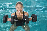 Fit blonde working out with foam dumbbells