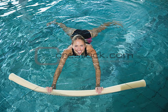 Fit blonde swimming with foam roller