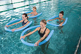 Fitness class doing aqua aerobics with foam rollers