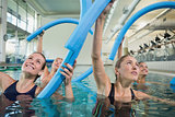 Happy fitness class doing aqua aerobics with foam rollers