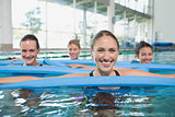 Female fitness class doing aqua aerobics with foam rollers