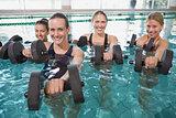Smiling female fitness class doing aqua aerobics with foam dumbbells