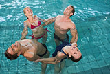 Happy fitness class stretching in aqua aerobics