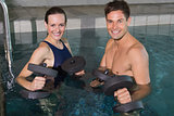 Happy couple working out with foam dumbbells