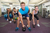 Muscular instructor leading kettlebell class