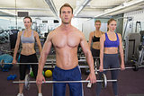 Fitness class lifting barbells together