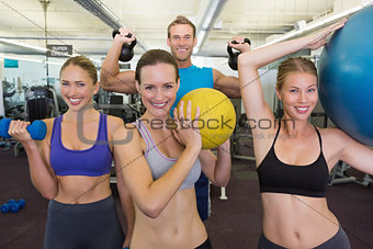 Fitness class posing with different equipment
