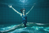 Athletic swimmer posing for camera and smiling underwater