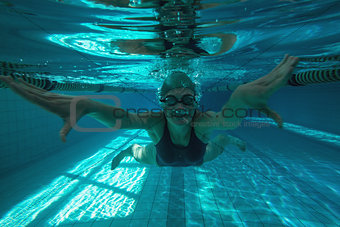 Athletic swimmer swimming towards camera