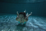 Pretty brunette smiling at camera underwater