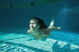 Pretty brunette smiling and swimming underwater