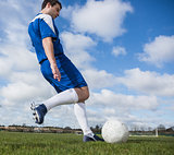 Football player in blue kicking the ball on pitch