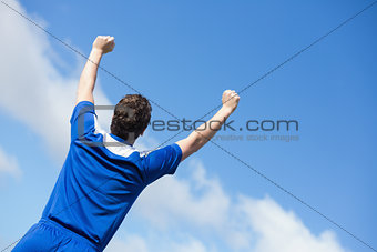 Football player in blue cheering