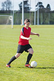 Football player in red playing on pitch