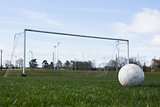 Football on an empty pitch in front of goal