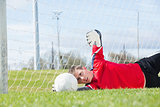 Goalkeeper in red making a save
