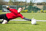 Goalkeeper in red saving a goal during a game