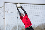Goalkeeper in red jumping up to save a goal