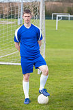 Football player in blue posing with the ball on pitch