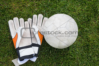 Goalkeeping gloves and football on pitch