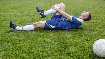Football player in blue lying injured on the pitch