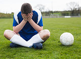 Disappointed football player in blue sitting on pitch after losing