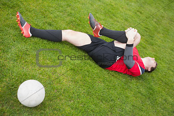 Football player in red lying injured on the pitch