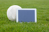 Football and tablet with blank screen on pitch