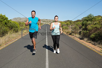 Fit couple jogging on the open road together
