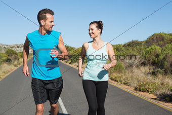Fit happy couple jogging on the open road together