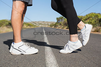 Fit couple standing on the open road together
