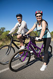 Active happy couple going for a bike ride in the countryside