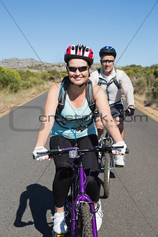 Fit smiling couple going for a bike ride in the countryside