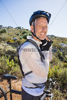 Fit cyclist adjusting helmet strap on country terrain smiling at camera