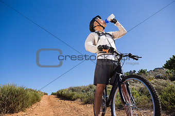 Fit cyclist drinking water on country terrain