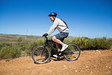 Fit cyclist riding on country terrain