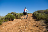 Fit cyclist pushing bike uphill on country terrain