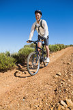 Fit cyclist cycling on country terrain