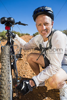 Smiing cyclist fixing his bike chain on country terrain