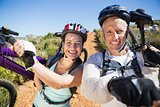Active couple carrying their bikes on country terrain together