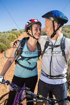 Active couple embracing on a bike ride in the country