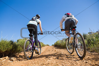 Active couple cycling uphill on a bike ride in the country